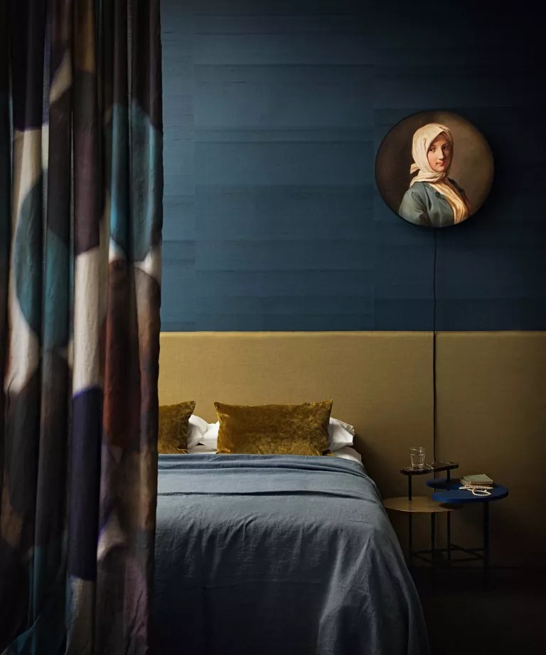 A bedroom with teal textured wallpaper, yellow ochre headboard and circular portrait painting on the wall