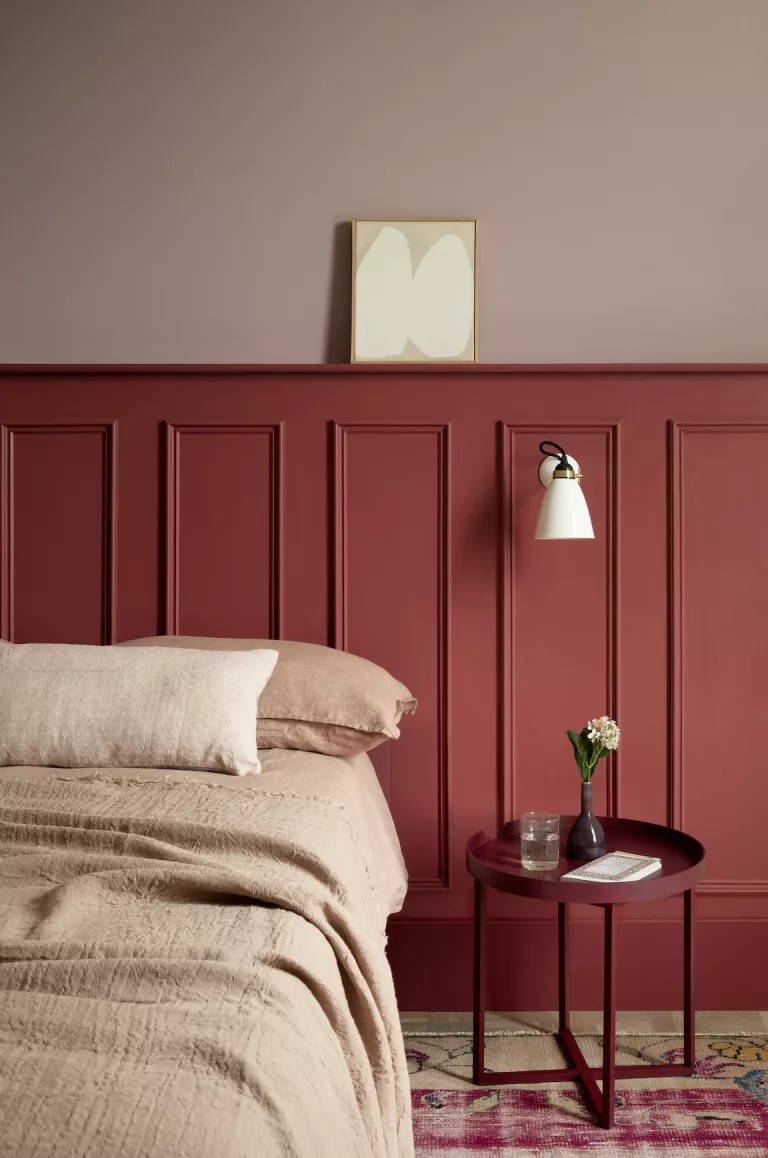 two tones of pink painted bedroom with linen bedding and wooden paneling