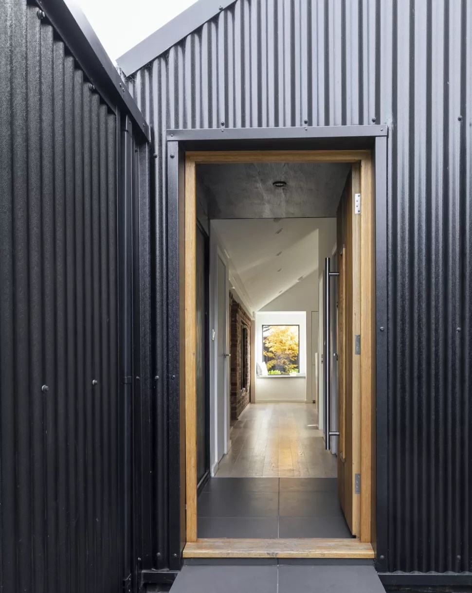 an exterior view of a small hallway idea leading through to a larger space