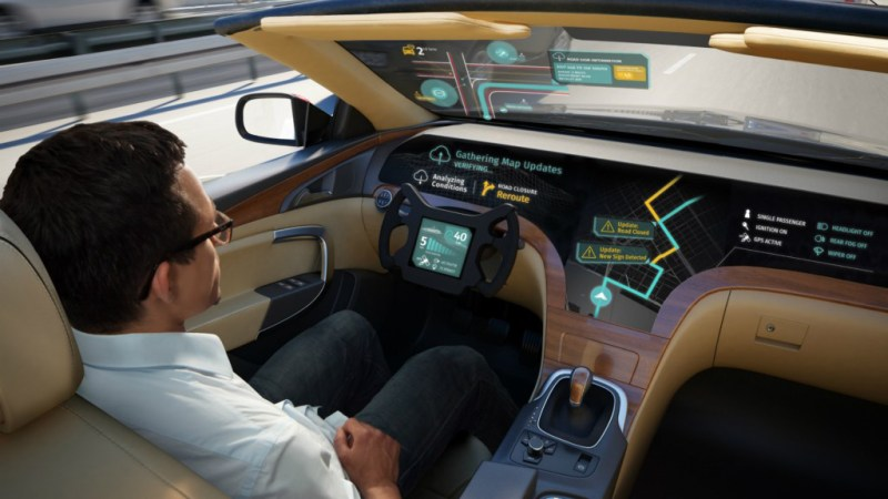 Man sitting in driver position in a driverless car