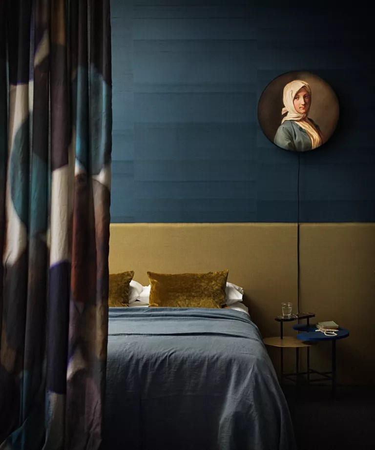 A bedroom with dark teal walls and a yellow ochre bedhead