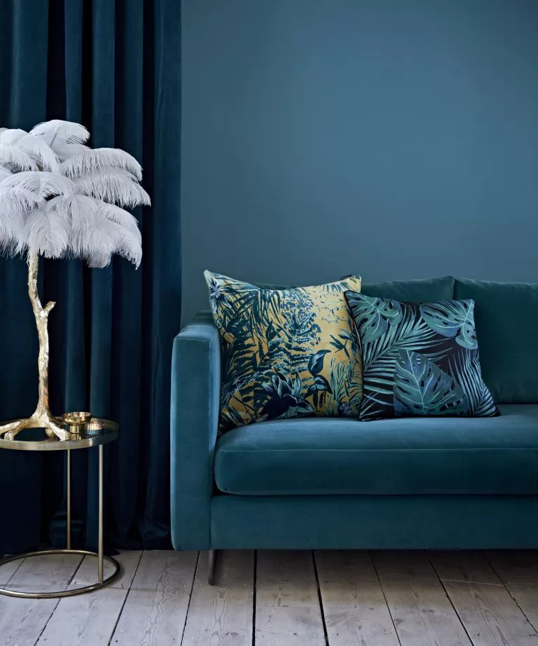 A living room with dark turquoise walls, blue velvet sofa and curatins and a gold side table with feather ornament
