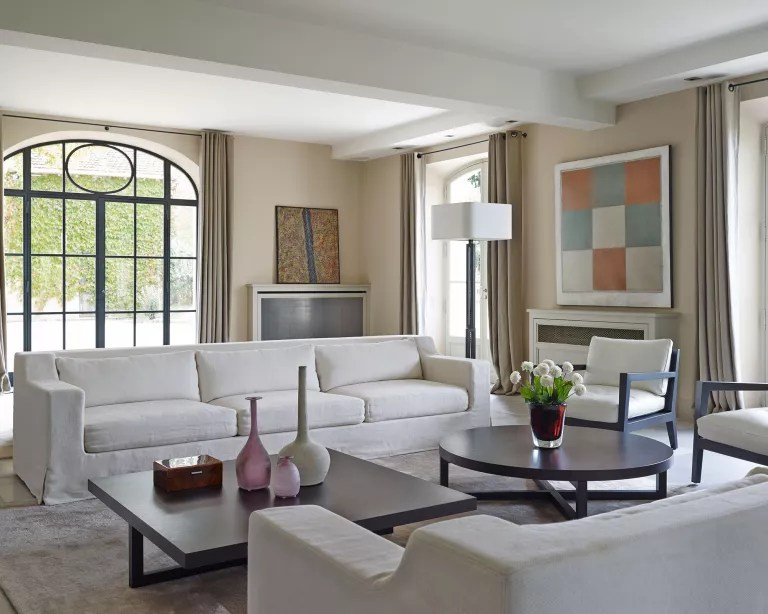 Living room with white sofas and cream walls