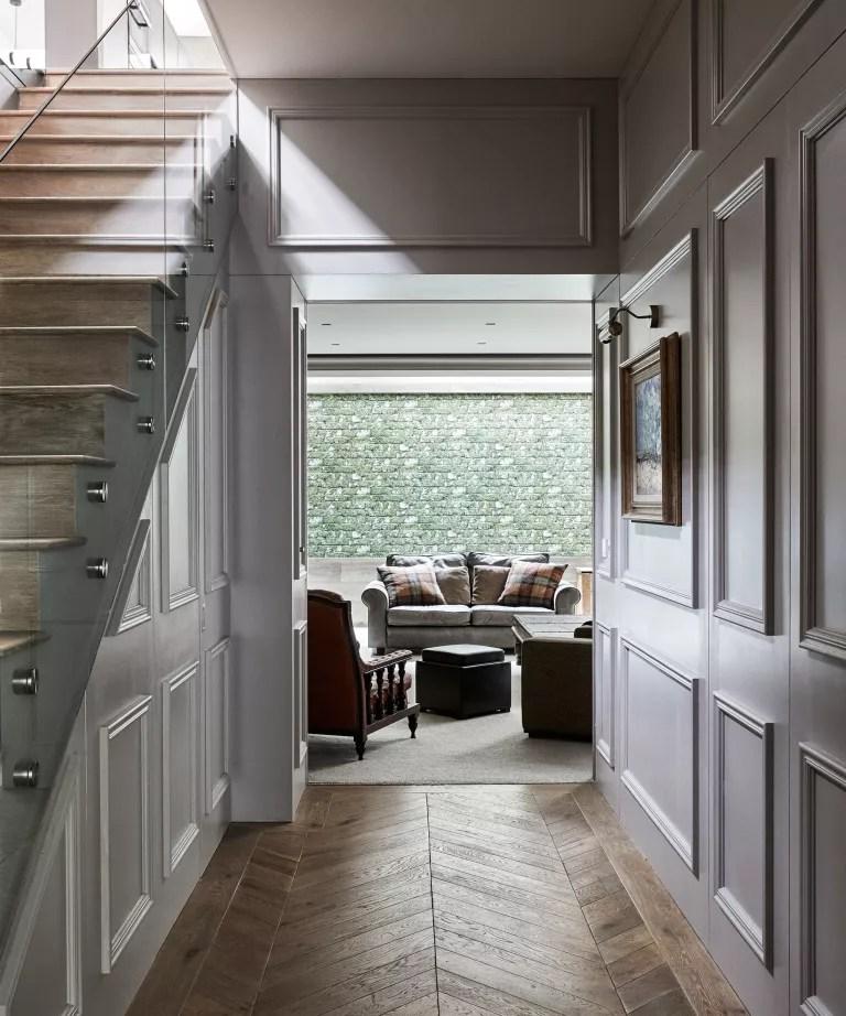 Hallway with herringbone floor looking towards a living space