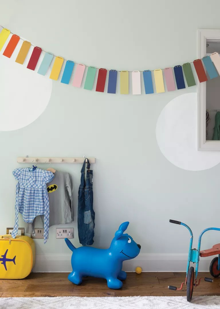 A child's playroom painted pale grey with large white dots
