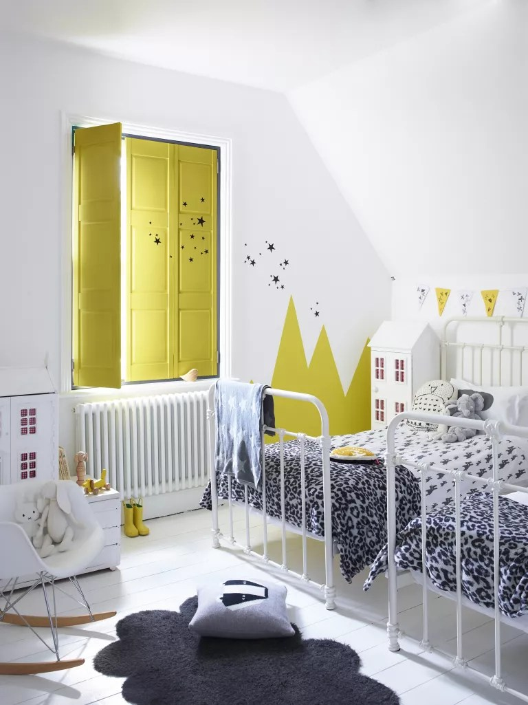 Pop of yellow on shutters in white shared bedroom ideas with leopard print blankets and black and white decor.