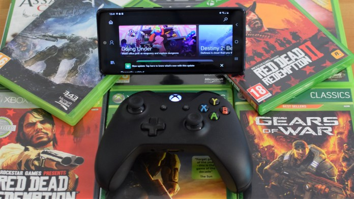 photo of a Samsung phone connected to an Xbox wireless controller resting on Xbox games