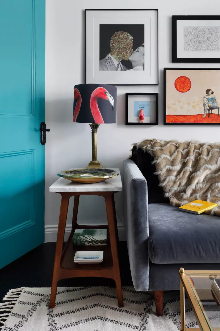 Living room with grey sofa, gallery wall and bright blue door