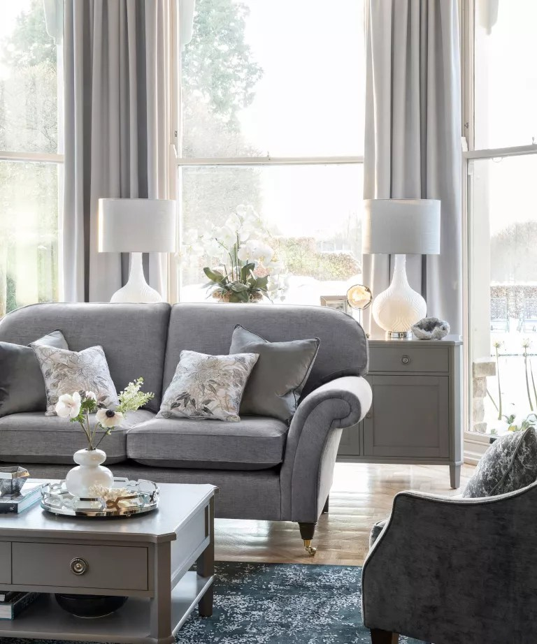 Gray sofa with patterned cushions in front of bay window with light gray curtains and gray cabinet with flowers and white/gray matching table lamps