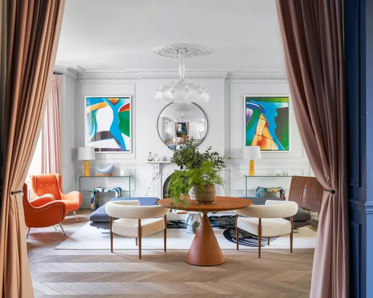 Mid-century modern style living room with modern art, white walls and curved chairs