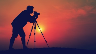 An image of a person taking pictures at sunset