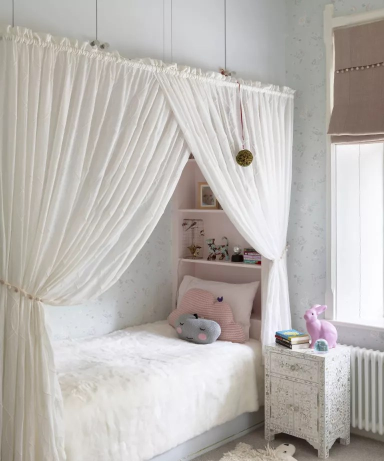 Kids room paint ideas with pale blue floral wallpaper and a recessed bed framed by white curtains