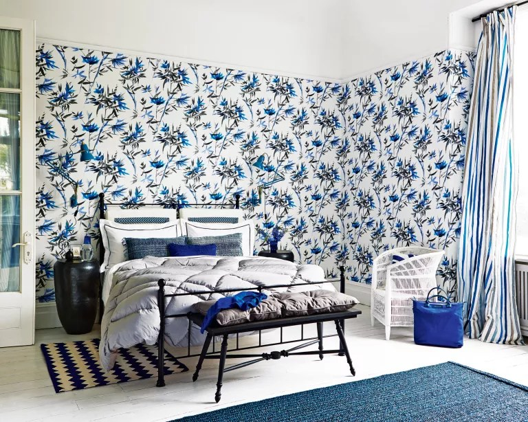 A bedroom with black, white and blue patterned wallpaper