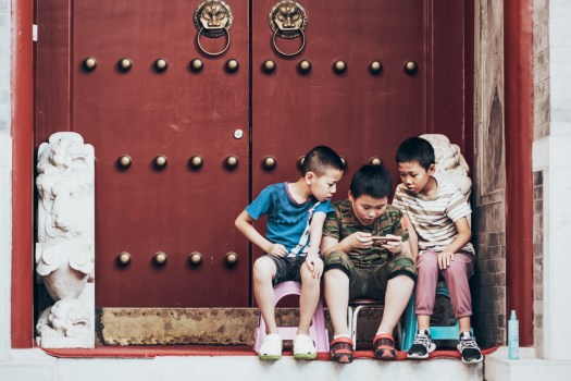 Three young boys gathered around a handheld device
