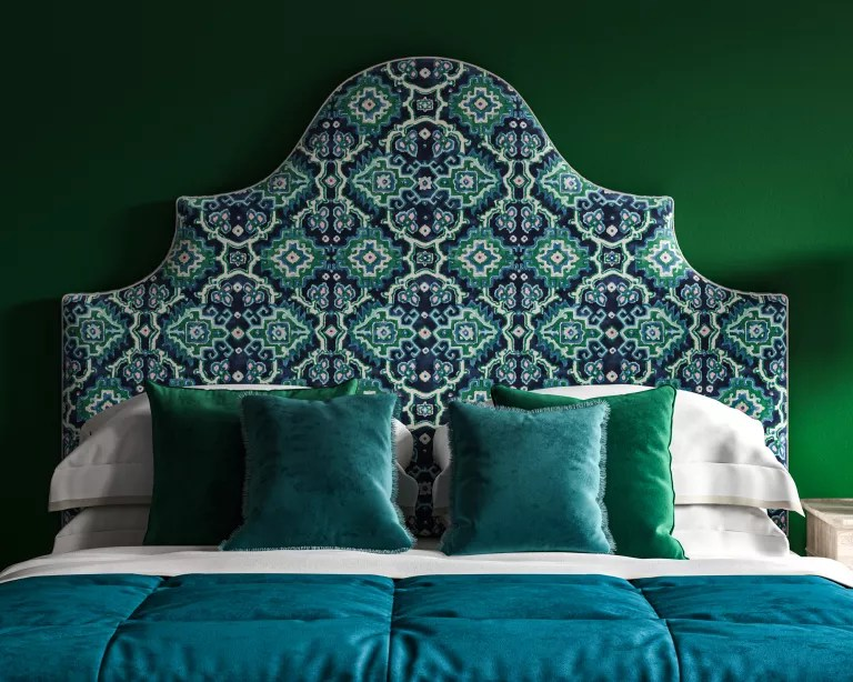 A dark green bedroom with a large upholstered headboard in a blue, white and green patterned velvet