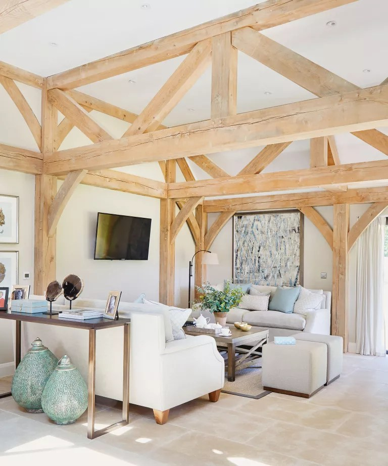 Country living room with wooden beams, white walls and TV