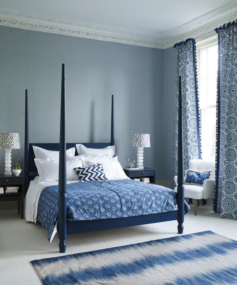 A bedroom with blue and white patterned wallpaper and a dark blue four poster bed