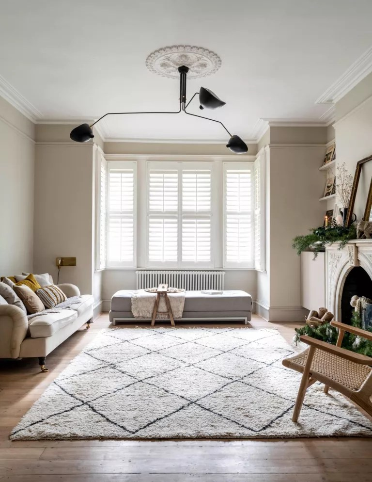 white living room with berber rug and shutters