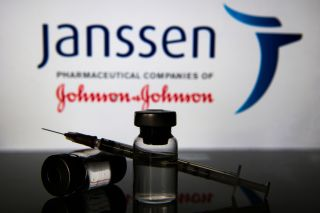 An image of two vials and a syringe in front of Johnson and Johnson's Janssen pharmaceutical companies sign.
