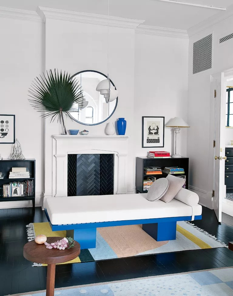 Modern white living room with day bed and fireplace with black painted floorboards