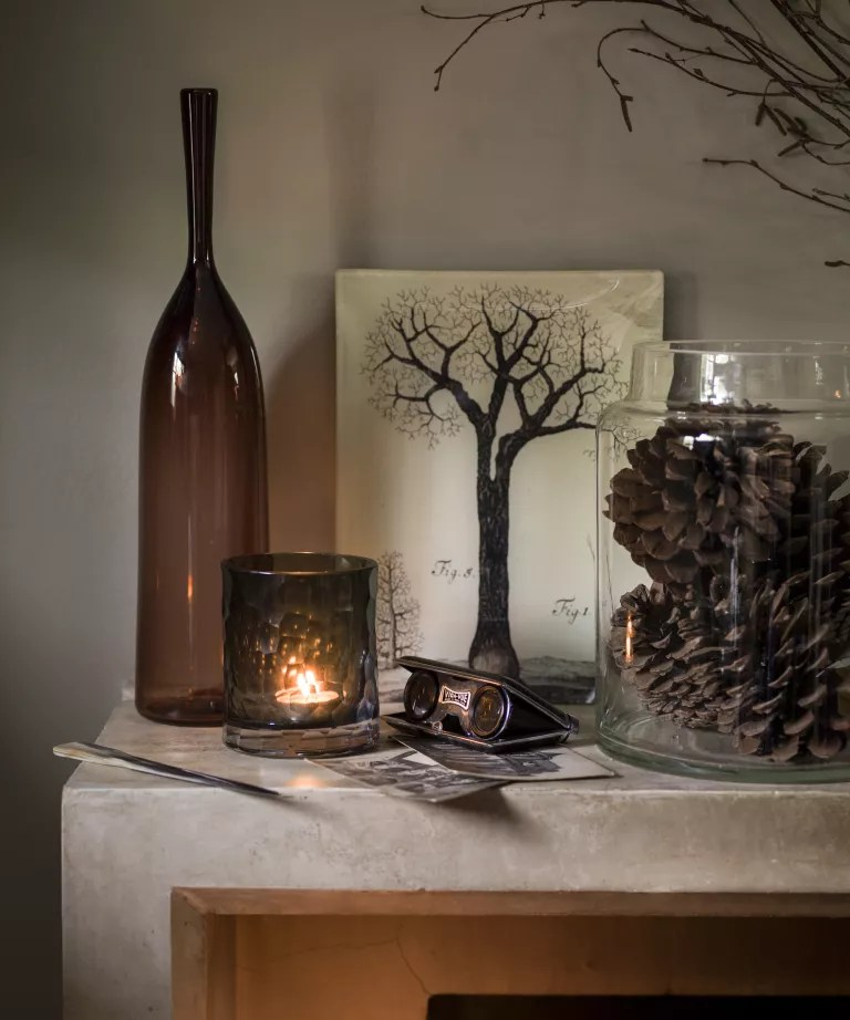 Fall mantel ideas with brpown glass bottle and candle holder, pine cones in a hurricane vase and tree painting