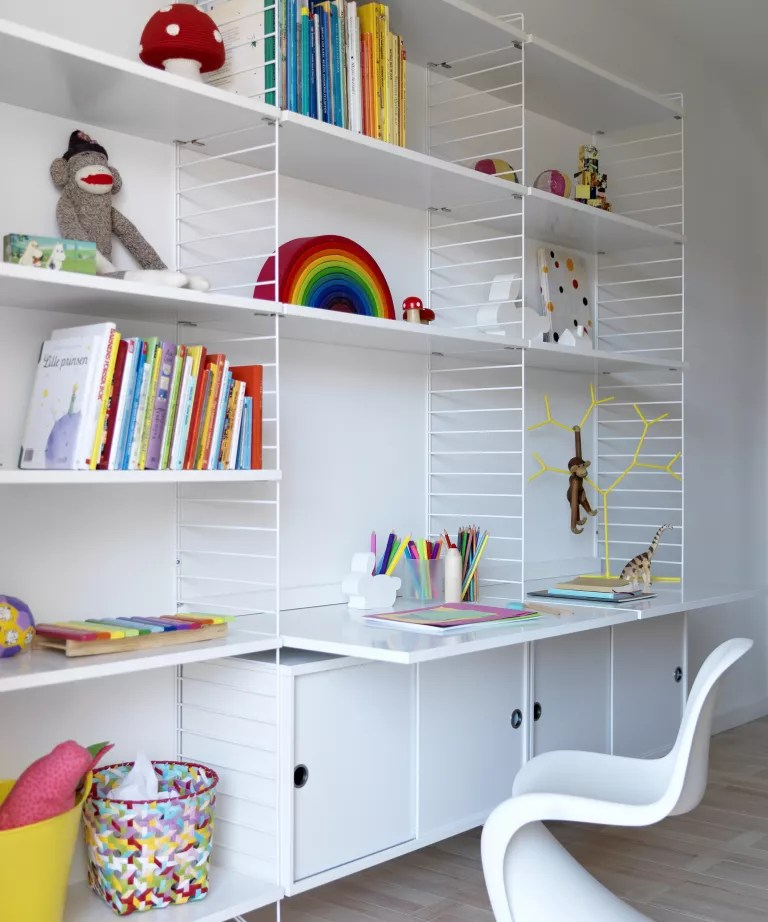 A child's bedroom with white walls, desk and open shelving unit