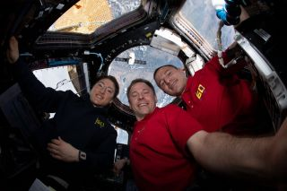 NASA astronauts Christina Koch (left), Nick Hague (center) and Andrew Morgan pose for a selfie inside the International Space Station's Cupola observation module as a SpaceX Dragon spacecraft hovers just outside in the background during their Expedition 60 mission.