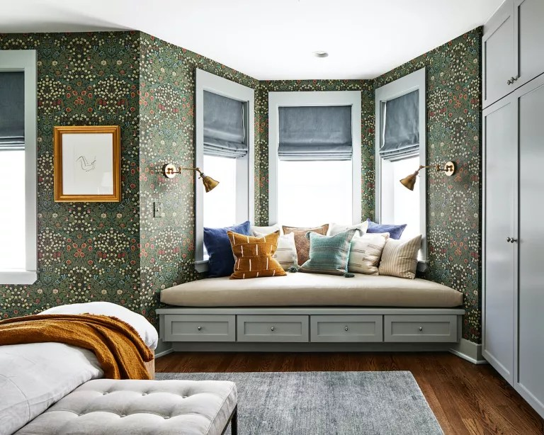 A bedroom with green floral wallpaper and a built-in storage seat in the bay window