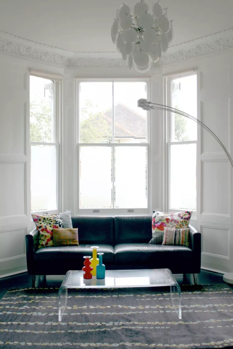 White bay window with frosted film in living room with gray carpet and blue couch
