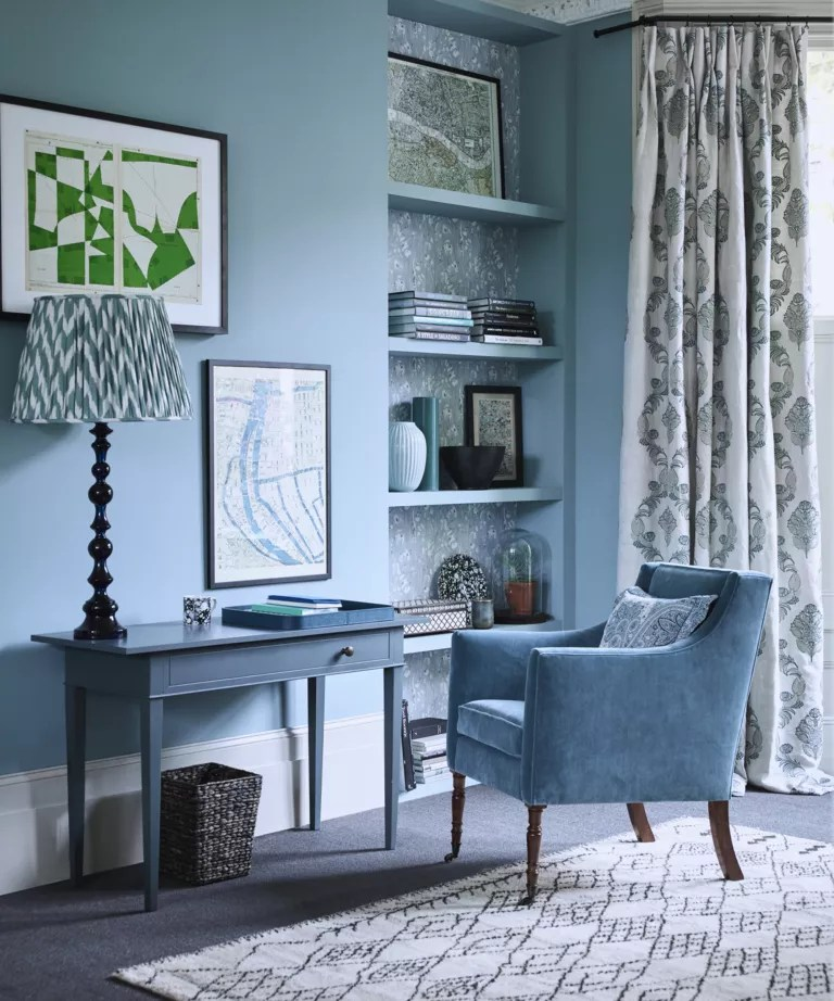 A living room with blue walls, a matching desk, armchair and bookshelf
