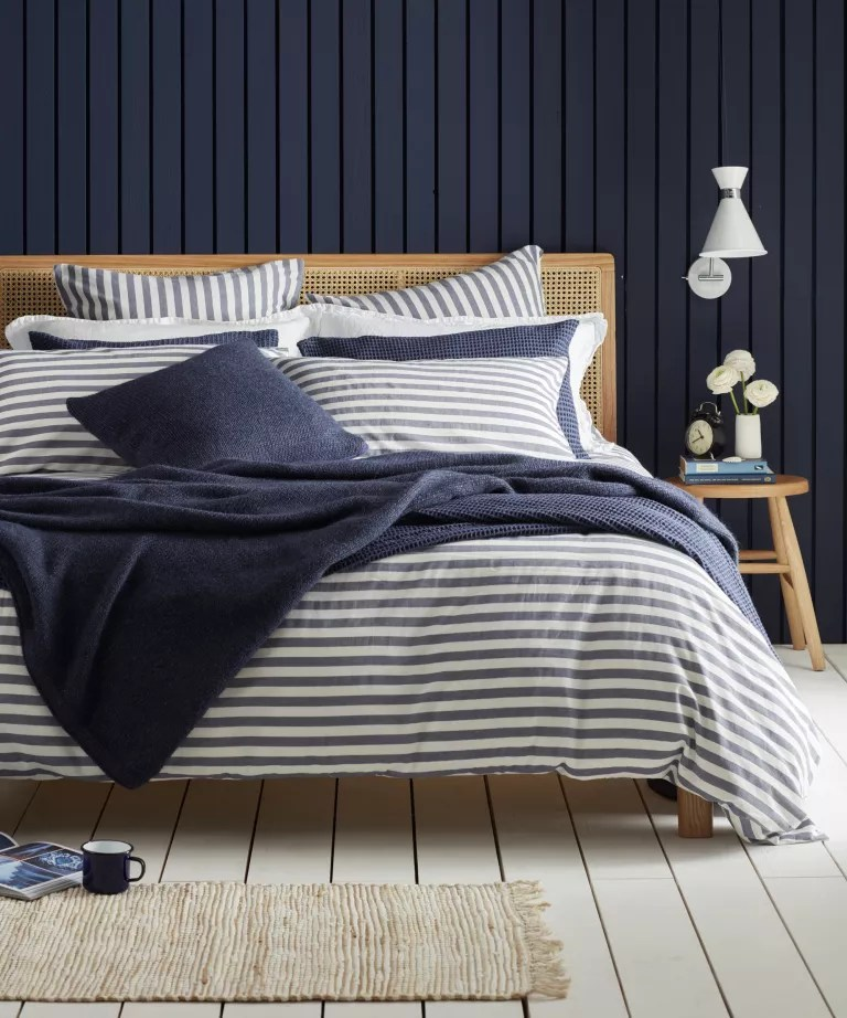 A bedroom with navy blue shiplap wall, and wooden bed with blue and white striped bedding