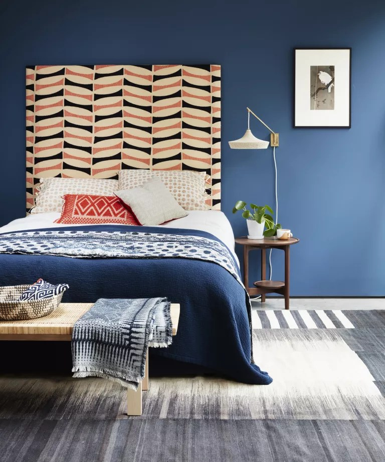 A bedroom with dark blue walls, a patterned orange and blue headboard and a blue and white woven rug