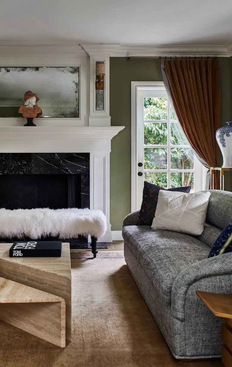 Green and white living room with large fireplace