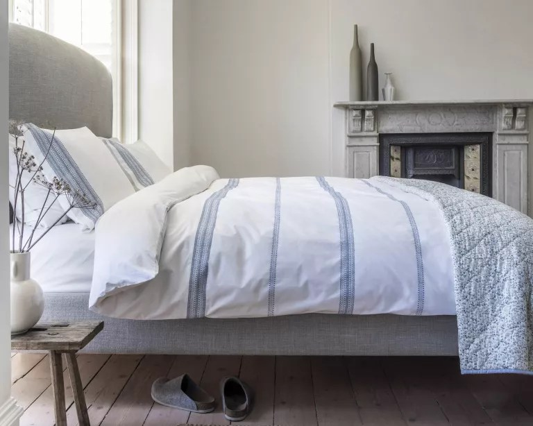 A bedroom with a grey marble fireplace, grey upholstered headboard and white and blue bed linen