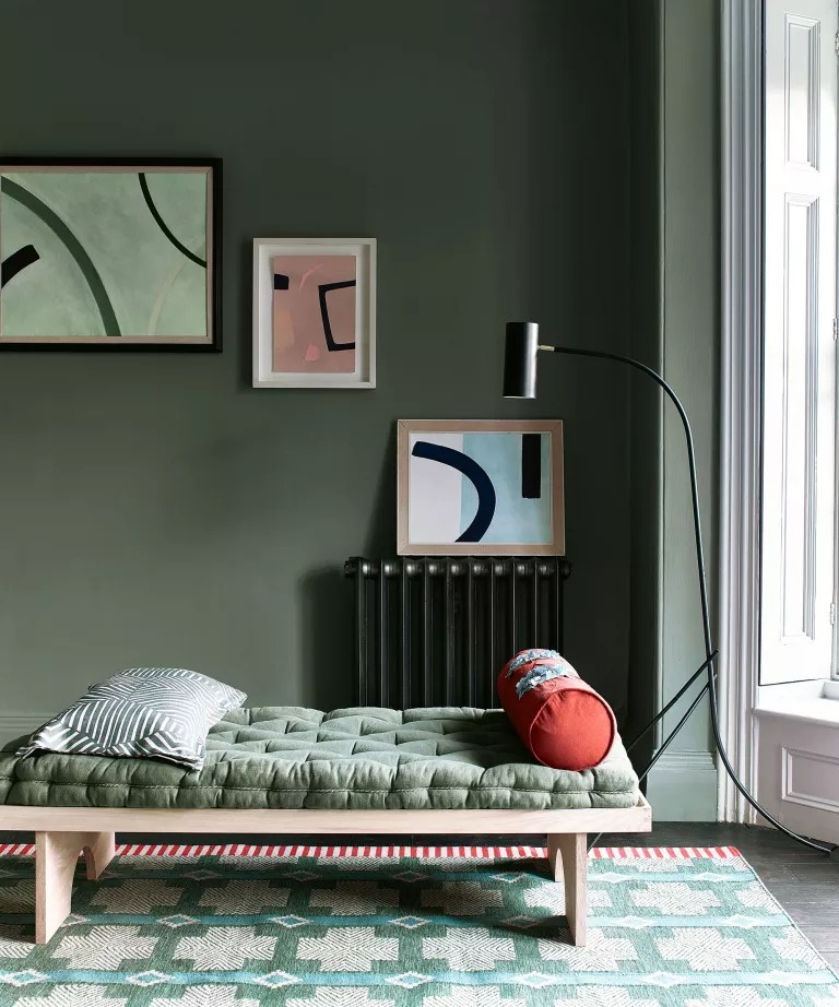 Dark living room with green paint and gallery wall