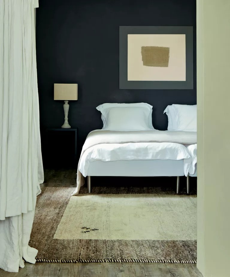 A bedroom with a black wall, white curtains and cream rug