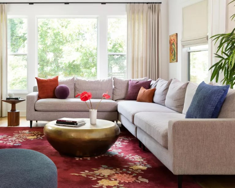 A living room with grey sofa, red rug and bright colored cushions