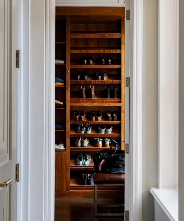 A bedroom with an open walnut closet with shoe shelves