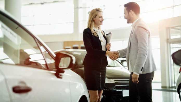 Salesperson shaking hands with customer in dealership showroom