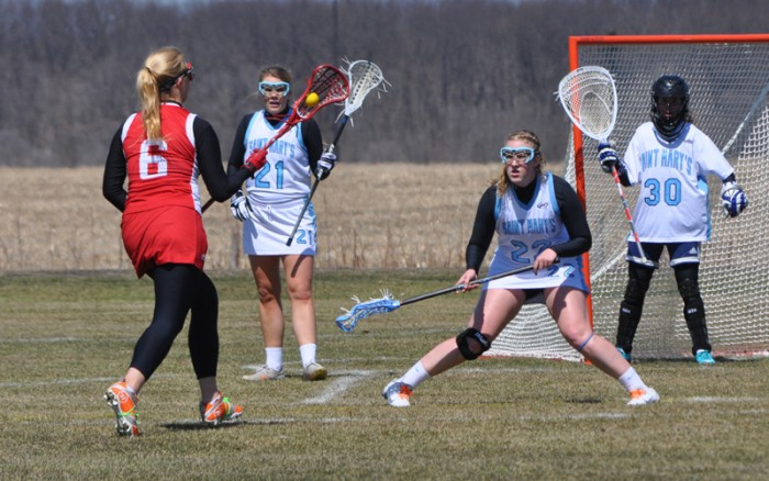 Belles sophomore defenseman Sarah Neeser (22) crouches in a defensive stance in the Belles' 16-4 win over Illinois Tech on Saturday. Neeser scored two goals in a 16-10 loss to Hope on Tuesday. Neeser has started every game for the Belles in their inaugural season.