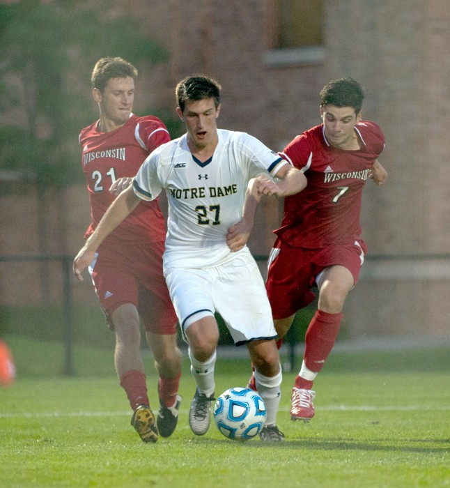Irish junior midfielder Patrick Hodan dribbles between two Wisconsin players in Monday's 5-1 win over No. 21 Wisconsin. Hodan tallied a goal in the  29th minute and an assist in the match's 49th minute.