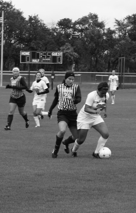 Belles sophomore forward Liza Felix holds off a Trine defender  during the Belles' 1-0 home win over the Thunder on Oct. 4.