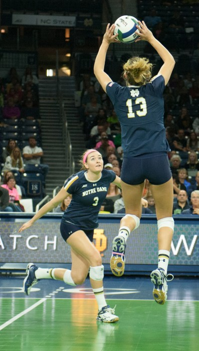 Irish junior setter Hanna Muzzonigro lays the ball up for freshman middle/right blocker Sam Fry at Purcell Pavilion on Oct. 5.