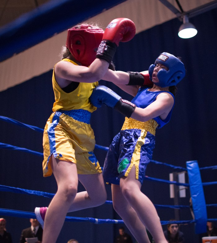 """Senior Amanda """"Boxing Panda"""" Leung connects on a jab to the body while absorbing a shot to the side of the head during her semifinal victory over sophomore Mia """"The Hulk"""" Hogan-Davis on Tuesday night. Leung won her final against Casey """"C My Fists"""" Gelchoin in a split decision Friday night at the Joyce Center Fieldhouse."""