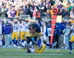 Irish wide receiver C.J. Prosise leaps over a defender to gain a few extra yards.
