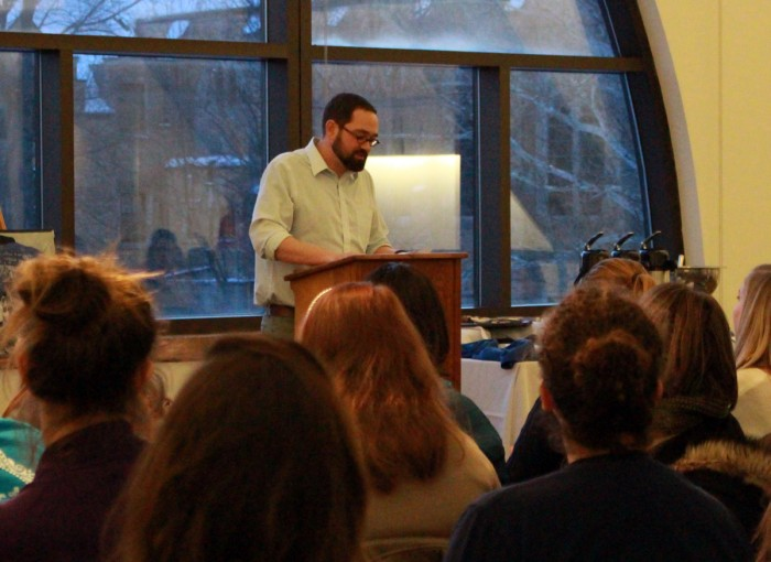 """Aaron Bremyer, head of the English writing center at Saint Mary's, reads a poem by a student during the """"Then and Now"""" poetry reading."""