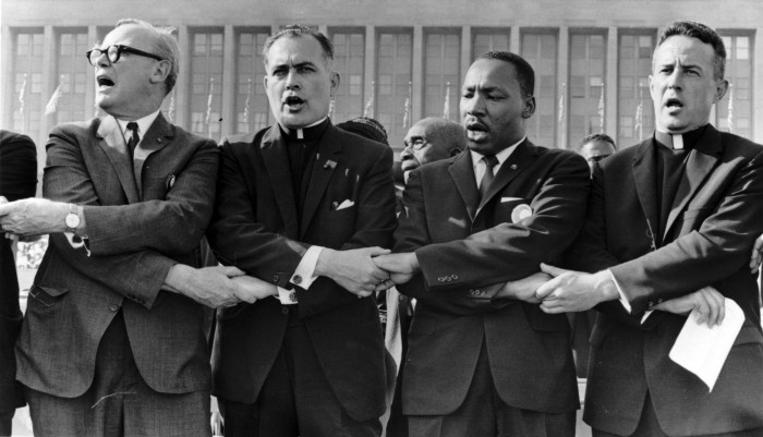 "Fr. Hesburgh, second from left, links arms with Dr. Martin Luther King, Jr., to his right, and sings ""We Shall Overcome"" during a 1964 civil rights rally at Chicago's Soldier field."
