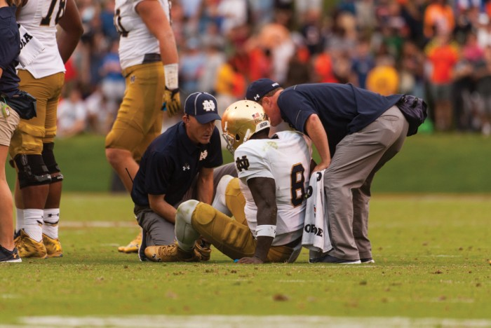 Irish junior quarterback Malik Zaire is surrounded by trainers after fracturing his ankle during Notre Dame's 34-27 win over Virginia on Saturday at Scott Stadium. Zaire threw for 115 yards and a touchdown in Charlottesville, Virginia, before going down with the season-ending injury near the end of the third quarter.
