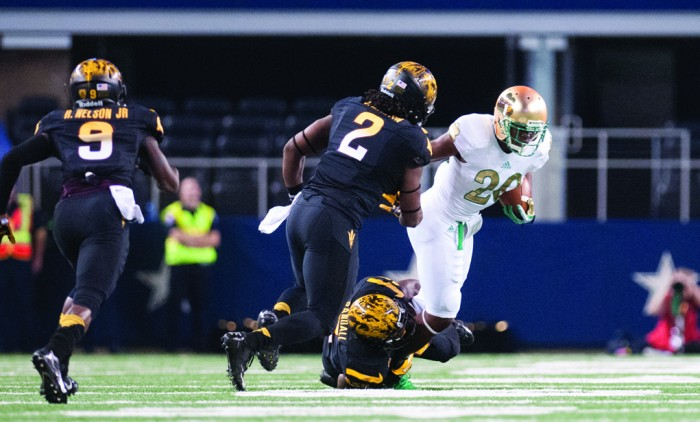 Irish senior running back C.J. Prosise tries to break an Arizona State tackle during Notre Dame's 37-34 win over the Sun Devils on Oct. 5, 2013. The game, part of Notre Dame's annual Shamrock Series, took place at AT&T Stadium in Arlington, Texas, home of the Dallas Cowboys.