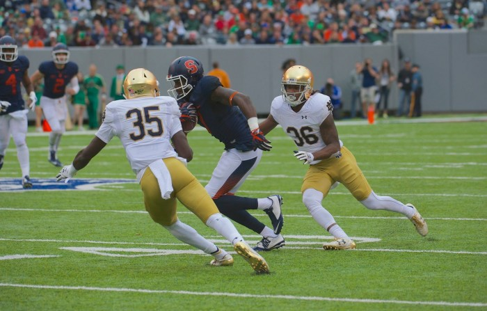 Freshman cornerback Donte Vaughn, left, and senior cornerback Cole Luke make look to tackle the ball carrier in Notre Dame's 50-33 victory over Syracuse at MetLife Stadium.